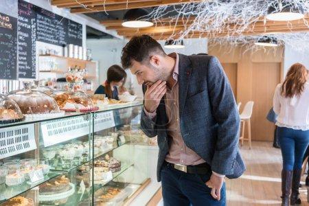 Photo pour Jeune homme indécis portant une tenue décontractée intelligente tout en regardant divers délicieux gâteaux exposés dans la vitrine d'un café moderne - image libre de droit