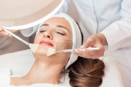 Beautiful woman during anti-aging facial massage in a modern cosmetic center