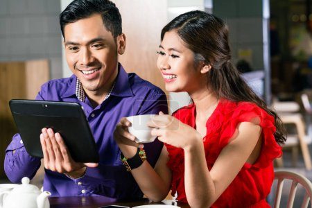Happy couple watching together an online funny video on a tablet