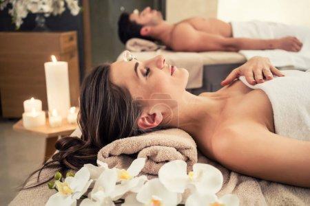 Photo pour Jeune homme relaxant avec son partenaire sur des lits de massage au spa moderne et centre de bien-être - image libre de droit