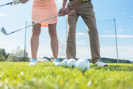 Photo pour Section basse de l'homme et de la femme tenant des clubs de fer, tout en pratiquant ensemble la bonne poignée et déplacer pour jouer au golf sur l'herbe verte d'un terrain professionnel - image libre de droit