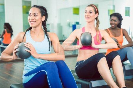 Photo pour Belle jeune femme exerçant russe twist avec boule med de position pour abs solide assise pendant les cours de groupe d'entraînement pour les femmes à la salle de gym - image libre de droit