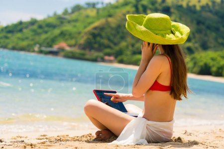Fashionable young woman talking on mobile phone while on the beach