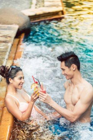junger Mann flirtet mit einer attraktiven Frau in einem trendigen Schwimmbad