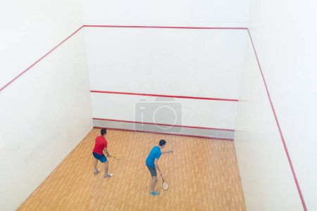 Rear view of two competitive young men playing squash game