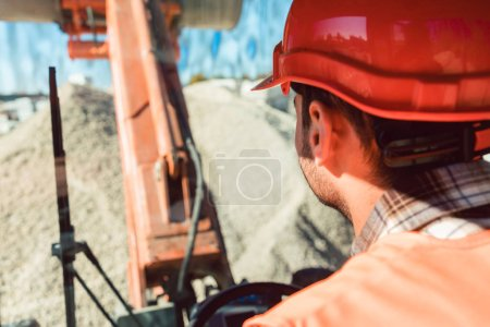 Worker on construction site operating wheel loader