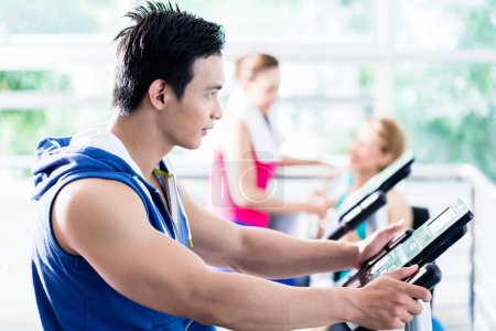 sportive man on treadmill flirting with smiling girls