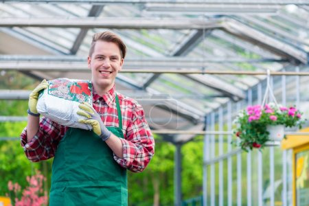 Cheerful young man carrying a bag of potting soil while working