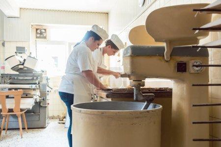Photo pour Gros plan sur boulanger en boulangerie formant du pain bretzel, une machine au premier plan - image libre de droit