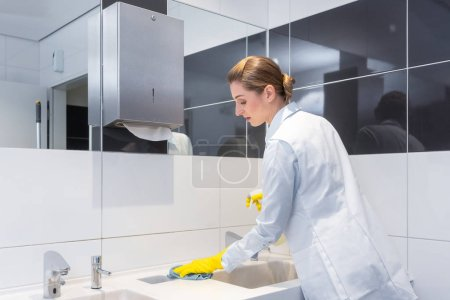 Janitor cleaning sink in public washroom
