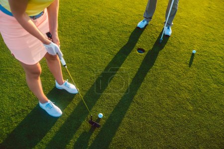 Photo for High-angle cropped view of a professional woman player, holding the putter golf club ready to hit the ball into the hole at the end of a difficult game with her partner or instructor - Royalty Free Image