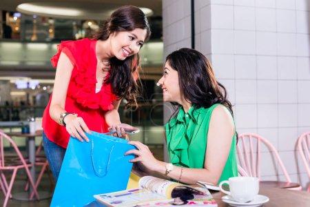 Photo pour Belle femme gaie montrant à sa meilleure amie son nouvel achat après une séance de shopping dans un café branché au centre commercial - image libre de droit