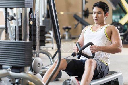 Determined young man looking forward while rowing at the cable machine
