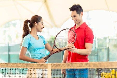 Tennis instructor teaching a beginner player the correct grip