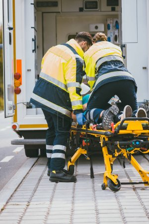 Paramedic on stretcher fighting for life of injured woman