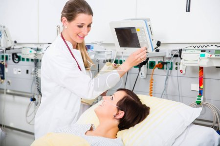 Doctor in intensive medical care checking results of woman patient