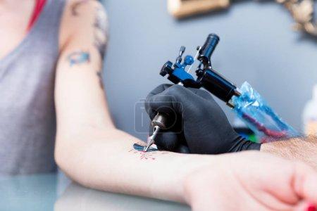 Photo pour Gros plan de la main d'un artiste de tatouage créatif ombrage un papillon coloré sur l'avant-bras d'un client femelle dans un studio modern - image libre de droit