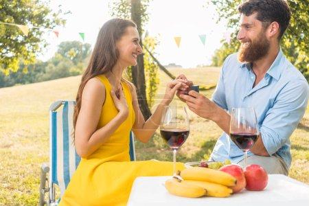 Belle jeune femme accepte avec joie et émotion la proposition de mariage de son petit ami au cours d'un pique-nique romantique dans une journée ensoleillée de l'été