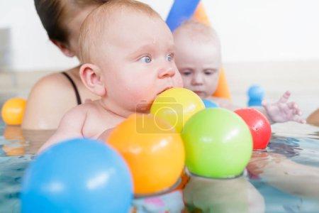 Photo pour Les mères et leurs enfants s'amusent à la leçon de natation de bébé entre beaucoup de boules d'eau - image libre de droit