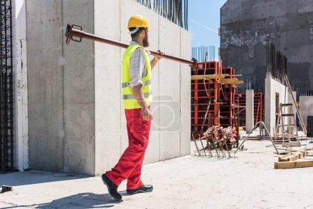 Photo pour Toute la longueur d'un ouvrier portant un équipement de sécurité, tout en portant une barre métallique lourde pendant les travaux sur le chantier d'un bâtiment résidentiel - image libre de droit
