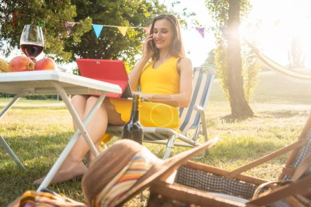 Successful female entrepreneur managing business sitting on picnic chair