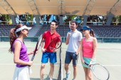 Four young and cheerful friends talking before starting a doubles match