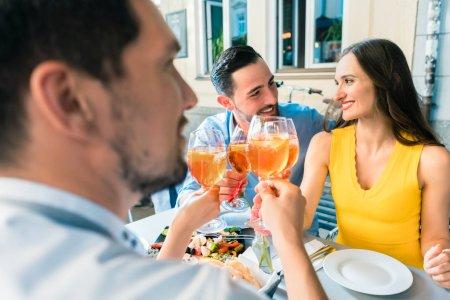 Foto de Cuatro amigos con tallo copas mientras tostar junto con un frío refrescante bebida alcohólica durante un delicioso almuerzo en el restaurante - Imagen libre de derechos
