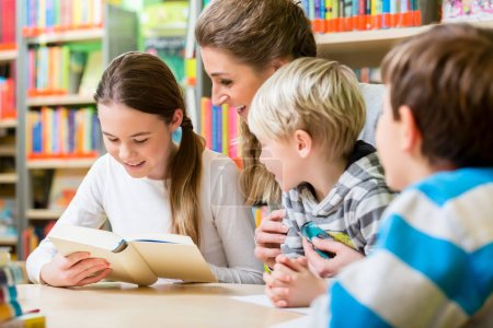Photo for Teacher with her class visiting the library reading books for education - Royalty Free Image