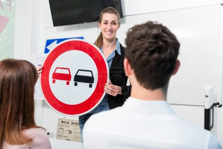 Photo for Driving instructor explaining meaning of street sign to class of students - Royalty Free Image