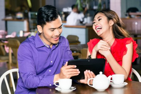 Photo pour Jeune homme beau avec le sens de l'humour regarder une vidéo drôle sur tablette PC à côté de sa belle petite amie dans un café moderne - image libre de droit