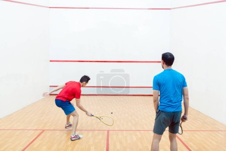 Photo for Rear view of two competitive young men with a modern lifestyle playing doubles squash game on a professional court - Royalty Free Image