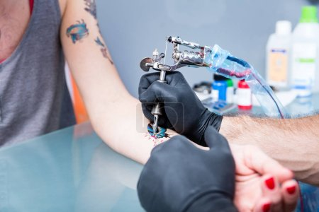Close-up of the hands of a skilled tattoo artist wearing black gloves