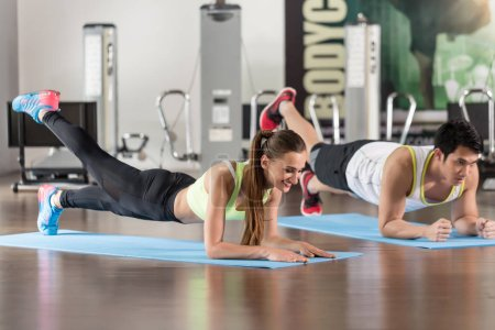 Determined woman exercising with her partner forearm plank at the gym