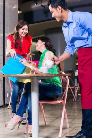 Photo pour Jeune femme à la mode portant des sacs à provisions tout en regardant heureux et surpris de rencontrer un ami dans un café à la mode - image libre de droit