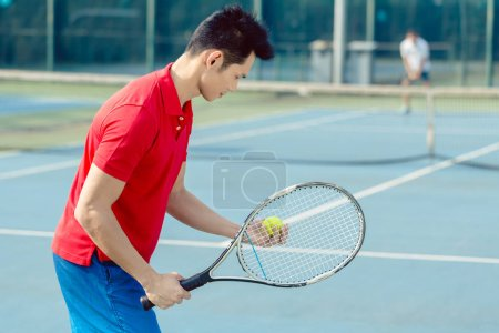 Asian tennis player looking at the ball with concentration before serving