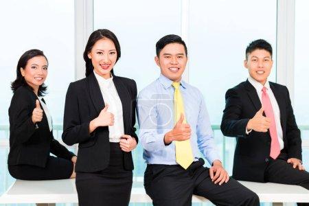 Photo pour Gros plan des gens d'affaires assis sur le bureau montrant une pancarte de pouce dans le bureau - image libre de droit