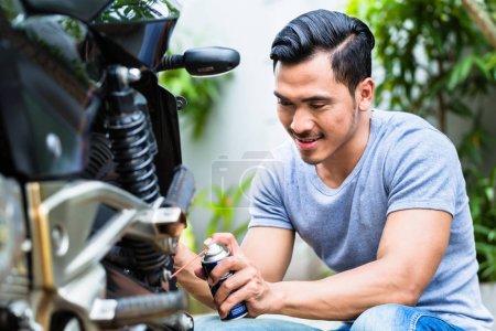 Man spraying grease in the motorbike