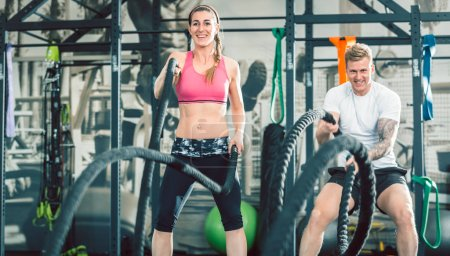 Two beautiful and strong women waving battle ropes during functional training