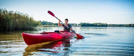 Photo pour Portrait d'un homme en kayak sur le lac idyllique à l'aide de la pagaie - image libre de droit