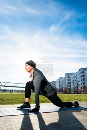 Determined young woman stretching her leg while kneeling on a mat