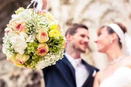 Photo pour Gros plan du bouquet de fleurs devant un couple souriant nouvellement marié - image libre de droit