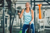 Strong woman exercising with battle ropes during functional training