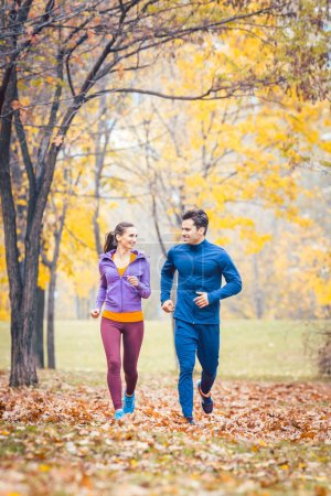 Photo for Man and woman running as fitness sport in an autumn park with colorful foliage - Royalty Free Image