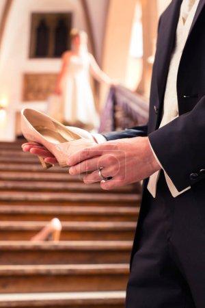 Bridegrooms hand holding brides wedding shoe