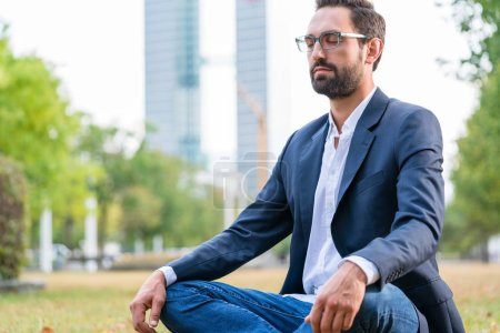 Photo for Close-up of calm businessman sitting in the park meditating - Royalty Free Image