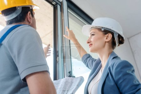 Photo for Architect woman and construction worker checking windows on site - Royalty Free Image