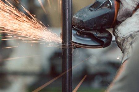Photo pour Travailleur dans l'usine de métal meulage pièce à usiner avec meuleuse à disque, étincelles volant - image libre de droit