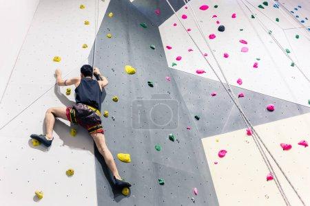 Photo pour Vue arrière du mur d'escalade de l'homme avec l'aide de la poignée - image libre de droit
