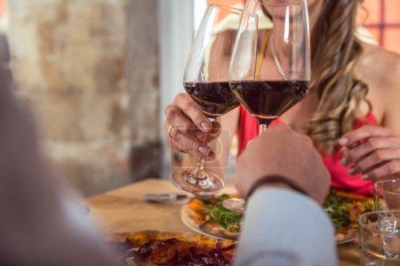Photo pour Gros plan du couple au restaurant grillé avec des verres de vin rouge - image libre de droit