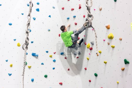 Photo for Rear view of man climbing wall without any protection - Royalty Free Image